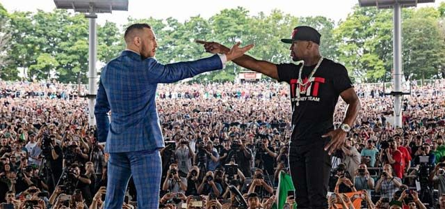 Mayweather and McGregor on stage pointing